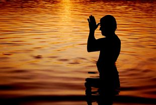 Early morning Sun worship (heliolatry) by a Hindu devotee, in the river Ganges in West Bengal, India.