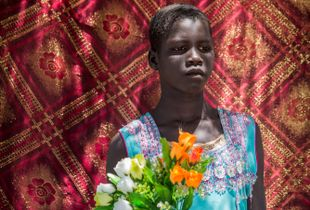 A girl with flowers in a UN IDP camp in Juba, South Sudan. 2016