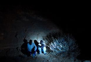African asylum-seekers wait for Israeli border patrol to pick them up, moments after they have illegally crossed the Egyptian border into Israel.