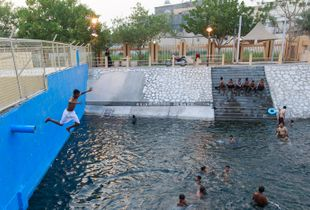 Kids jump from a high spot in the pool
