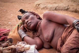 Old Himba woman with toys and artefacts made for selling