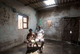 Agbavi, Togo. Komlan Setor (man), 27 and Adjo Setor, 25, sit in their house on the coastline of Agbavi. Due to the depletion of fish stocks, Komlan is struggling to feed his family and is now forced to work part-time as a tailor. With their house just on the shoreline, Komlan predicts his family will be forced to move in 6 months time.