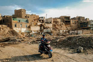 A motorist ride past the original of old city of Kashgar before it was demolished by local authorities.