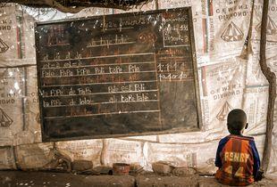 A kid sitting on a concrete bench on a school in the slums of Ouagadougou (Burkina Faso)