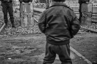 A Syrian boy tries to intimidate the Greek police at the border.