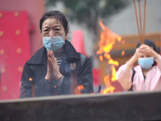 Local resident prays for peace  in a temple in  China