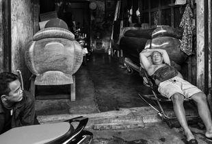 A coffin maker takes a nap outside his workshop, Bangkok 2017