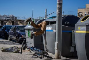 Almeria, Spain. A young North-African immigrant, during his weekly combing of downtown waste containers.