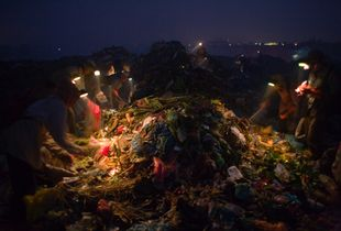 Recycling workers, picking through the waste for plastic bags, in the middle of the night, on Smokey Mountain Rubbish Dump. They rent miner's lamps and batteries for 25 cents, which is about a quarter of what they will make on a night shift. © Nigel Dickinson.