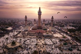 November 7, 2017 - Two birds fly past the minarets of the Great Mosque in Touba, while thousands of people gather on its square. It's the evening before the Grand Magal Festival starts. Every year, 2-3 million people gather in Touba for this pilgrimage to commemorate Cheikh Amadou Bamba Mbacké (1853-1927), who was the founder of the Sufi order of the Mourids and is worshiped as a Saint.