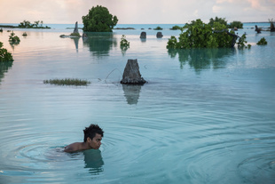 Peia Kararaua, 16, swims in the flooded area of Aberao village that is located in Tarawa atoll, Kiribati. Kiribati is one of the countries most affected by sea level rise. During high tide many villages become inundated making large parts of them uninhabitable.