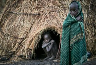 Young Mursi boys, slowly waking up in the morning