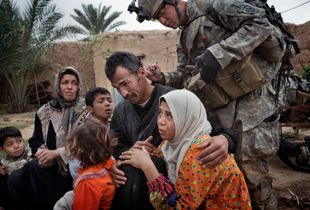 Qubah March 24, 2007. A US soldier marks the hands of women and the backs of the necks of men with numbers according to their neighborhoods. Lt Col. Andrew Poppas of the 73rd Calvary, 82nd Airborne Division, said the numbering system allowed troops to determine if people were moving around the village of Qubah despite a lockdown following a US attack on insurgents. © Yuri Kozyrev/NOOR