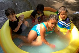 kids in inflatable pool, west harlem block party