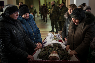 Family members mourn the body of a dead Separatist fighter at a mass funeral in the rebel-held town of Stakhanov, Eastern Ukraine.