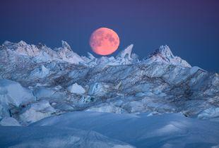 Arctic moon rising over icebergs, Greenland