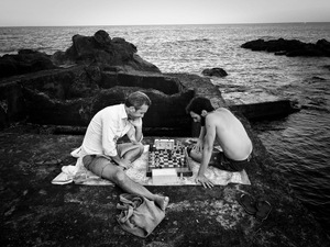 Capomulini, Sicily. Father and Son. A game of chess on the lava, by the deep sea.
