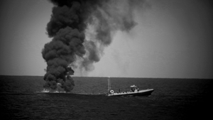 At Sea. Central Mediterranean. Fuocoammare: Fire at sea. An empty migrant boat, after the rescue of its occupiers,  is set on fire by a Libyan coastguard patrol.