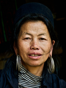 Lady from the Black H'mong minority wearing the traditional small circular black headpiece and several large silver earrings.