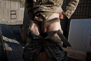 A U.S. Army soldier from Charlie Company, 2-28 Infantry, 172nd Infantry Brigade poses with ammunition belts used for underwear at Combat Operations Post Margah in Paktika Province on September 3, 2011. © Adam Ferguson