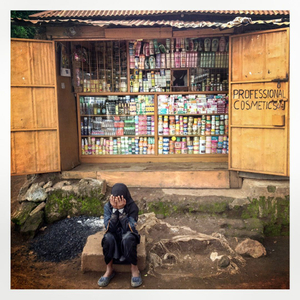 A young woman holds her head in her hands as she sits oin front of a shop in Kibera. The Kibera slum is the largest slum in Nairobi with around half a million inhabitants.