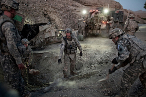 U.S. Army Soldiers from the 276th Engineer Battalion attempt to clear the scene of an Improvised Explosive Device (IED) attack on a Mine Resistant Ambush Protected Vehicle (MRAP) in the Tangi Valley, Wardak Province, Afghanistan on September 8, 2009. Three U.S. soldiers were evacuated by air after being injured in the attack. © Adam Ferguson
