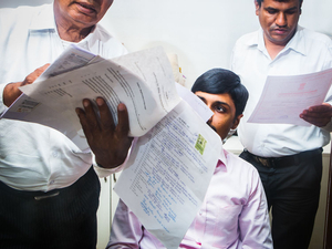 Two customers are simultaneously talking to an employee about their contracts. [Municipal Corporation, Gandhinagar]