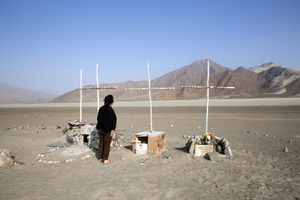 On the side of the Pan-American Highway, Otilia León Velásquez, the sister of Gilmar Ramiro León, looks at the crosses that mark the spot where, in 2011, the remains of Gilmar and the other eight men were found and exhumed in 2011. Huanca Corral, Santa, 2013