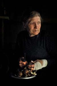 A woman peels potatoes at a farm in Mirashkhani.
