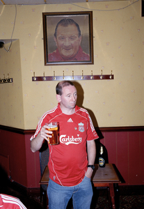 Liverpool Supporter in front of picture of Bill Shankley, Anfield, Liverpool 13 May 2007.