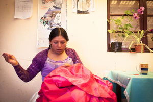 Reyna Torres sews a skirt that was damaged during a fight. Cholitas use their everyday clothes even on the ring.