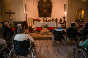 Guests on wheel chair gathering in front of the Villa Cenacolo's church altar, to pray the new born Jesus at the end of the Christmas mass.