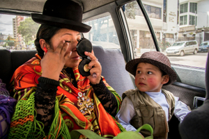 Juanita La Cariñosa puts make up on a taxi ride on the way to a fight while her son looks at her.