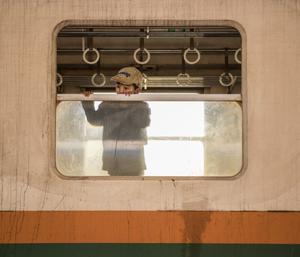A kid peeking out of the circle train wagon in Myanmar
