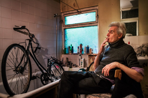George is taking a cigarette break from repairing one of his bikes. Due to the limited space in his house, his bathtub is the most convenient location for repairing bikes.  © Corinna Kern
