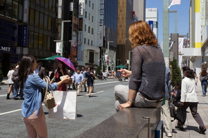 woman sitting on top of subway entrance wall