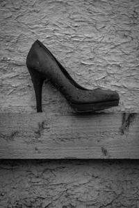 A womans shoe sits upon the fence  inside of the camp.
