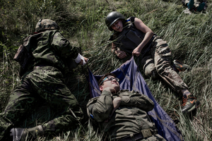Volunteers are training to carry away a wounded soldier.