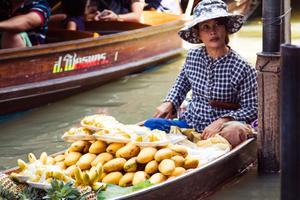 Woman selling fruit at Damnoen Saduak Floating Market.  Ratchaburi, Thailand (4/2017)