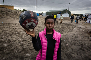 August 2015, Calais, France. A refugee from Eritrea plays with a ball while he waits for a chance to go to the ferry's to the UK. Many refugees want to go to the UK because they have family there, speak English or hope for good job opportunities.