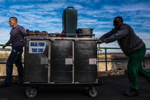 Prisoners transport food in special containers and bread crates from the main kitchen through the prison to a wing to be served.  HMP/YOI Portland, Dorset.