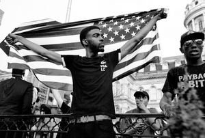 Baltimore, Md- A young protester holding the American Flag during the March For Peace.