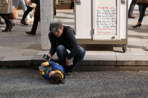 infant playing game on handheld game console lying on street