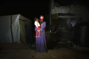 26 years old mother Heba Fareed Abu Jama'a and her daughter Moha Hussein, 2 years and 3 months, pose at their destroyed house due to Israeli attack during the summer's 50-day war. Since there is no space to move, or too expensive to do so, they have to live at a tent next to the house, with 8 other persons. Al-Zana'a, Khan Yunis.