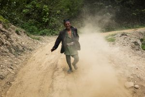 A villager tries to get a ride with the aid distribution truck.