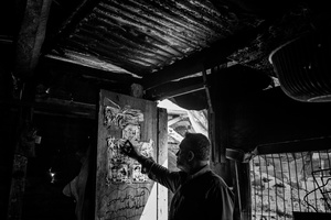 A man points at his son martyr' poster in a makeshift house where he lives in Al Shejaiya neighborhood of Gaza city.