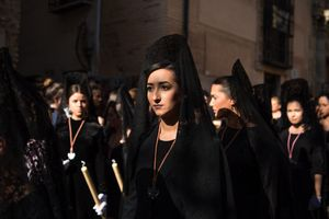 Young women in traditional veil wait for the procession to continue.