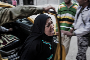 A woman, getting out of a taxy, is screaming the name of her son, wounded by a mortar shot.