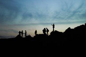 Young Palestinian men stand on rocks at sunset at Gaza seaport, Gaza Strip, 2014.