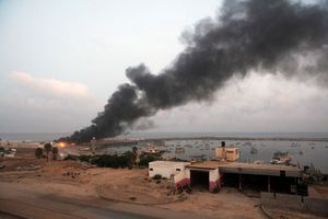 Smoke rises above the sea port of Gaza city after an Israeli attacked buildings of fishermen, Gaza city, 2014.